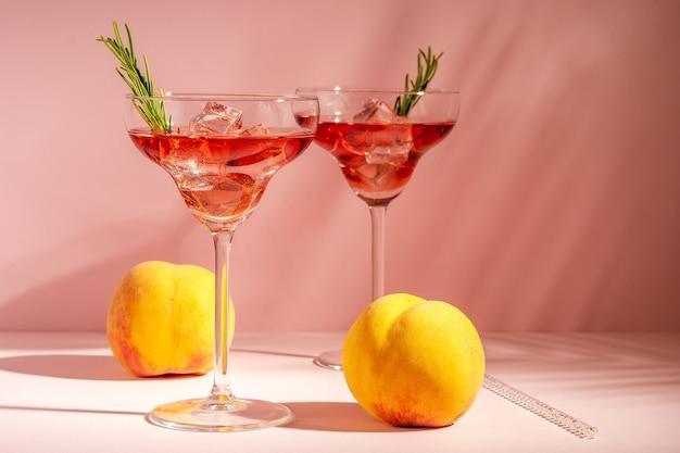 Cóctel refrescante en un vaso con un melocotón sobre un fondo brillante