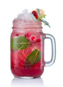 Coctel rojo del alcohol con los arándanos en el tarro de consumición aislado