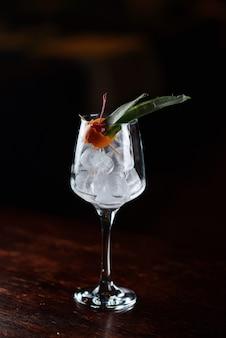 Cóctel rojo con hielo y cereza en un vaso transparente. líquido vertido en un vaso