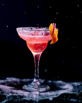 Cóctel rojo con piel de naranja pelada y cubitos de hielo picados.