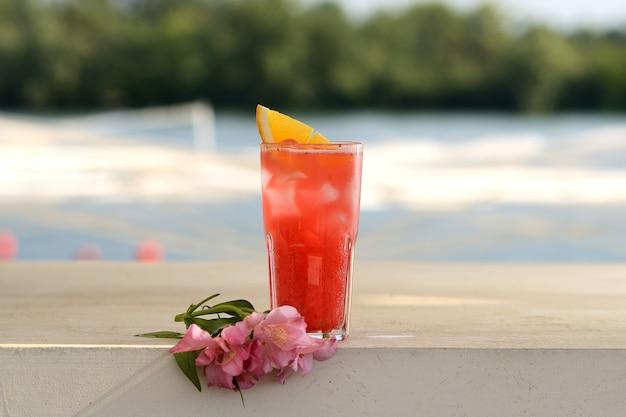 Cóctel rojo en un vaso con una rodaja de naranja. con decoración floral