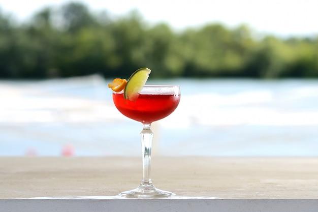 Cóctel rojo en un vaso de vidrio con una rodaja de limón. con decoración floral