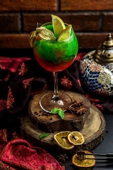 Cóctel rojo y verde cubierto con limón