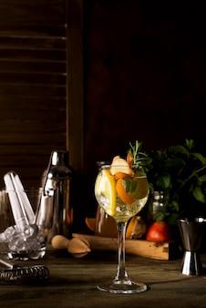 Cóctel con romero, limón y naranja sobre fondo de madera oscuro