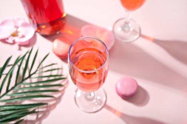Cóctel rosa tropical de verano decorado con flores de orquídeas rosadas, macarrones y hojas de palma.