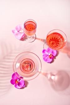 Cóctel rosa tropical de verano en vasos diferentes decorados con flores de orquídeas rosadas.
