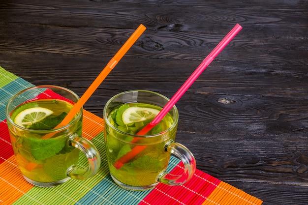 Cóctel de té frío con menta y limón en dos tazas de vidrio transparente sobre una mesa de madera oscura.