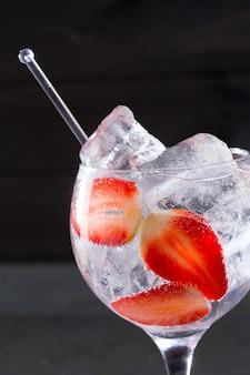 Cóctel de tónica de gin con fresas hielo macro primer plano