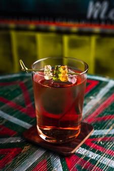 Un cóctel transparente en un vaso alto con un gran cubo de hielo adornado con ositos de goma