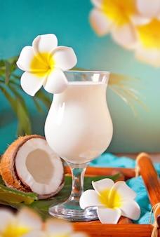 Cóctel tropical exótico caribeño tradicional bebida piña colada en vasos con flores de plumeria frangipani, hojas de palma y coco en la superficie. concepto de picnic de playa tropical.