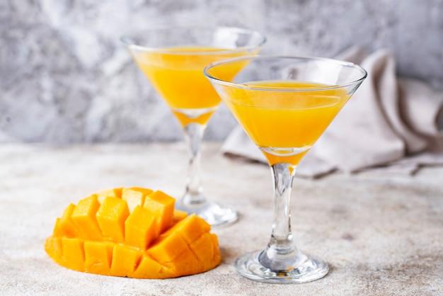 Cóctel tropical con mango sobre fondo claro
