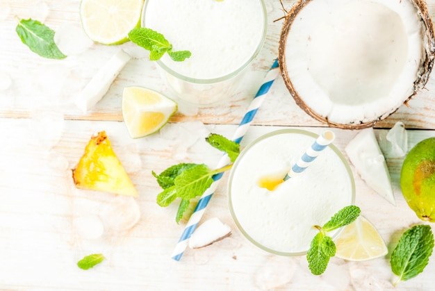 Cóctel tropical, piña colada, piña y coco mojito o batidos, con lima y menta, sobre un azul claro