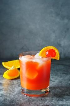 Cóctel de verano. zumo de naranja con menta, sirope, rodajas de fruta y cereza con hielo.
