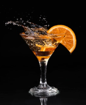 Cóctel de vermut dentro de copa de martini sobre fondo oscuro