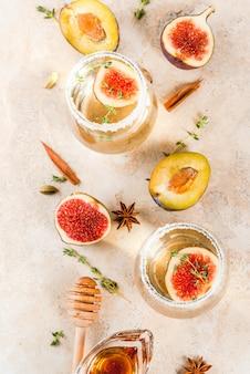 Cóctel de vino blanco dulce frío de otoño con ciruela, miel y tomillo