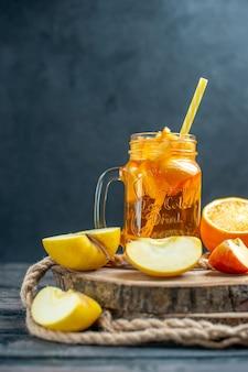 Cóctel de vista frontal cortadas naranjas y manzanas en tablero de madera en la oscuridad