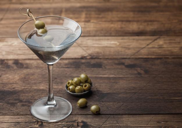 Cóctel de vodka martini gin en vaso original con aceitunas en recipiente de metal y palos de bambú sobre superficie de madera. espacio para texto