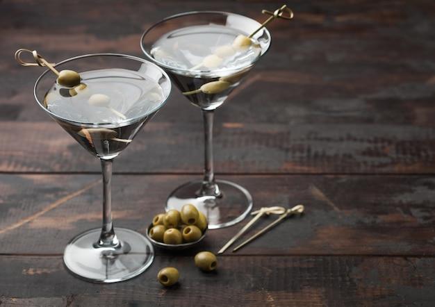 Cóctel de vodka martini gin en vasos originales con aceitunas en recipiente de metal y palos de bambú sobre superficie de madera oscura.