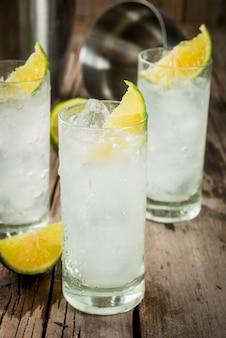 Cóctel de vodka y tónica highball con guarnición de lima sobre una vieja mesa rústica de madera