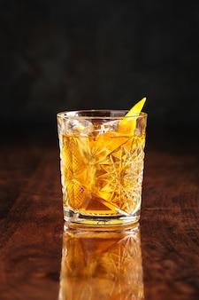 Cóctel de whisky en mesa de madera con reflejo