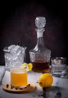 Cóctel de whisky sour en bandeja de madera con cáscara de limón en el borde, fondo con cubitera, botella de whisky y dosificador. mesa de madera vieja y fondo de material oxidado
