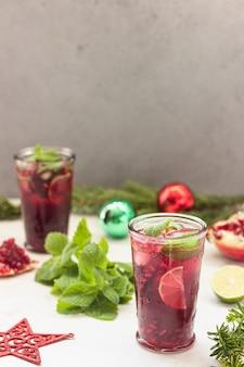 Cóctel con zumo de frutas, lima, menta, granada y hielo.