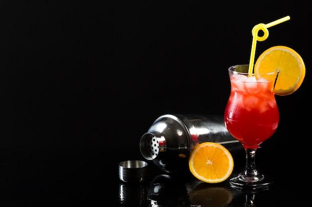 Coctelera y copa de cóctel con espacio de copia y naranja