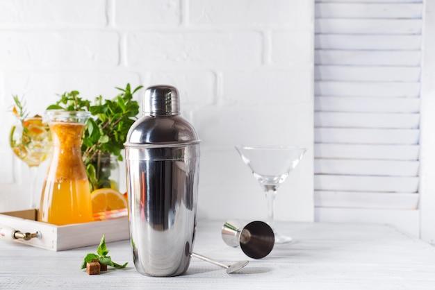 Coctelera, licor, pinzas y cuchara con hielo en un cubo para preparar un cóctel de verano