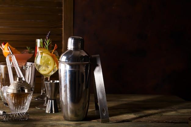 Coctelera, licor, pinzas y cuchara con hielo en un cubo para preparar