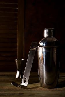 Coctelera, licor, pinzas y cuchara con hielo en un cubo