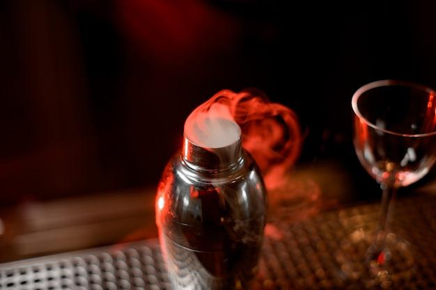 Coctelera con mezcla humeante y vidrio sobre mostrador