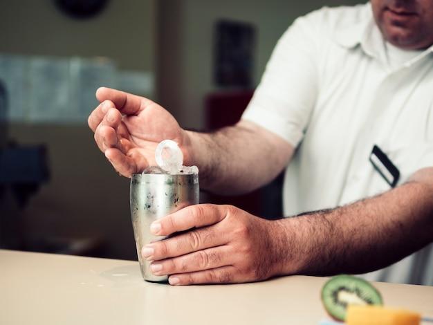 Coctelera de relleno del camarero de sexo masculino con los cubos de hielo