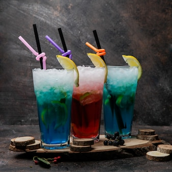 Cócteles de alcohol de primer plano copas de cóctel de laguna azul decorado con limón y copa de cóctel con whisky en un soporte de madera