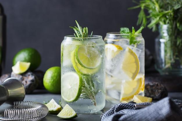 Cócteles duros de agua mineral con lima y limón y accesorios de bartenders