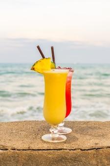 Cócteles helados bebiendo vaso con mar y playa