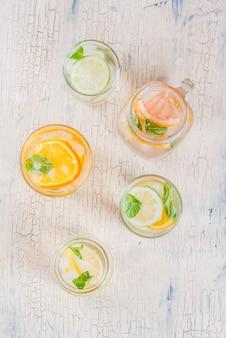 Cócteles saludables de verano, conjunto de varias aguas infundidas de cítricos, limonadas o mojitos, con lima, pomelo, naranja, bebidas dietéticas de desintoxicación.