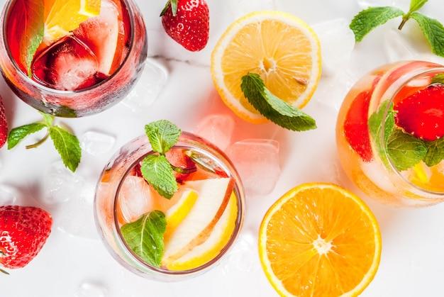 Cócteles de sangría fría, blanca, rosa y roja con frutas frescas, bayas y menta