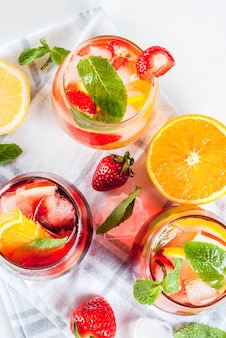Cócteles de sangría rosa y rojo blanco frío con frutas frescas, bayas y menta.