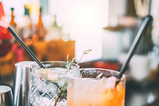 Los cócteles se sirven en la barra de bar preparada con ginebra, romero, papper y jugo de naranja.