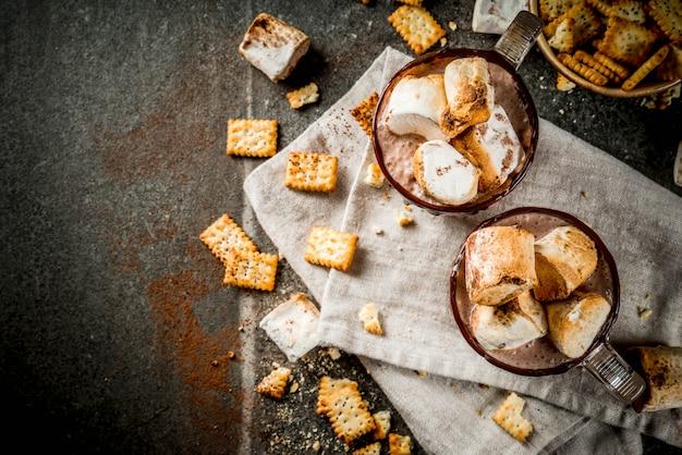 Cócteles tradicionales de otoño e invierno, alcohol. cóctel de ponche de huevo de chocolate caliente con galletas saladas y malvavisco asado, en dos tazas, sobre una mesa de piedra negra, vista superior