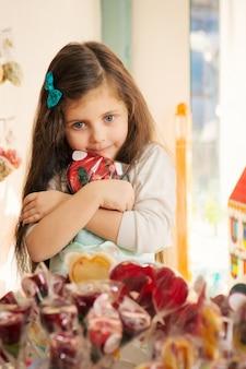 Codicia niña con piruleta en tienda de golosinas