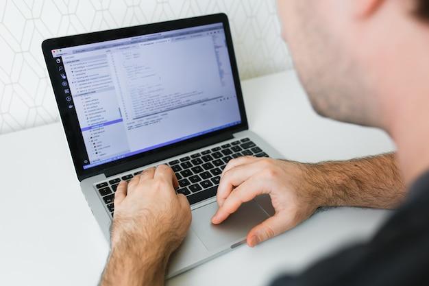 Codificación de primer plano en pantalla, manos de hombre que codifican html y programación en computadora portátil con pantalla, desarrollo web, desarrollador