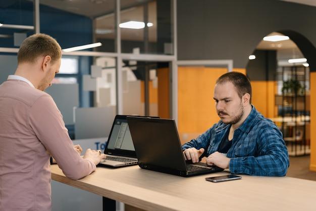Codificadores de ti trabajando en la computadora portátil en la oficina de pie en la mesa