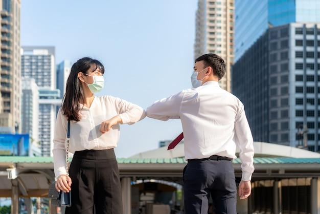 El codo es un nuevo saludo para evitar la propagación del coronavirus. dos amigos de negocios asiáticos se encuentran frente al edificio de oficinas.