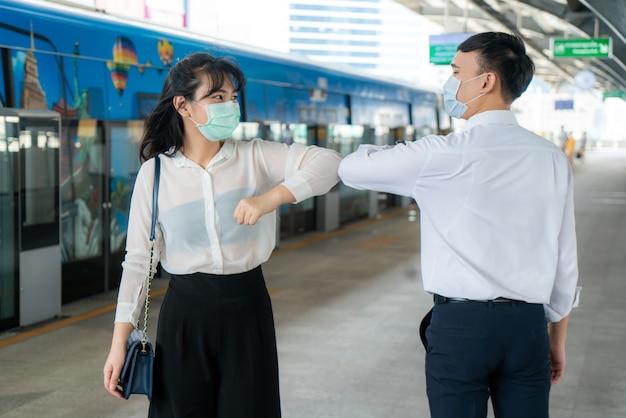 El codo es un nuevo saludo para evitar la propagación del coronavirus que dos amigos de negocios asiáticos se encuentran en la estación de metro.