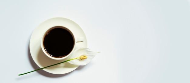 Cofe americano con flor sobre la superficie blanca
