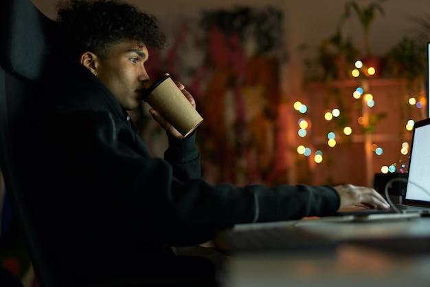 Coffee break vista lateral del joven con piercing bebiendo café sentado en la mesa frente a