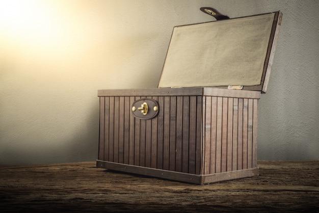 Cofre de madera viejo con abierto iluminado en tablero de madera contra la pared del grunge