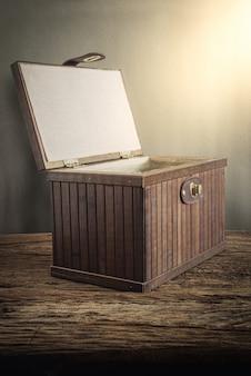 Cofre de madera viejo con abierto iluminado en tablero de madera contra pared grunge