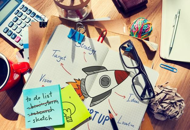 Cohete dibujado en un cuaderno en una mesa desordenada